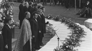 Lapuan patruunatehtaan räjähdysonnettomuuden uhrien hautajaiset 24.4.1976. Siunaustilaisuus Lapuan tuomiokirkon pihalla: neljäkymmentä arkkua,  siunaukseen valmistuva papisto arkkujen ääressä, presidentti Urho Kekkonen hautajaisvieraana.