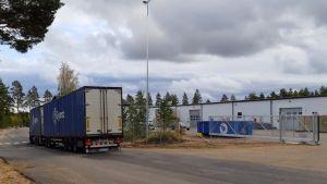 En avlång, låg, vit industribyggnad. Till vänster en blå långtradare.