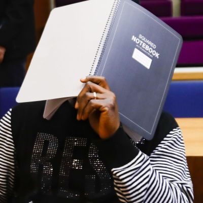 En man täcker sitt ansikte med en pärm i en rättegångssal.