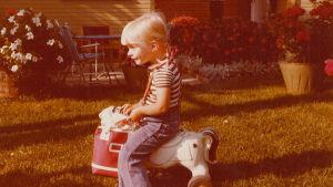 Tiina Jauhiainen lapsena ratsastamassa leikkihevosella.