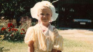 Roh Petas i gulvit klänning, ljusröda örhängen och vit hatt med breda brätten. I början av 1990-talet