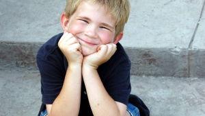 Poika hymyilee rappusilla istuen