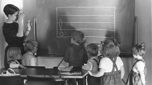 Lasten musiikkileikkikoulu. Opettaja ja lapset liitutaulun ääressä.