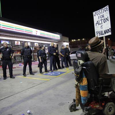 Mies pyörätuolissa osoittaa mieltää poliisien edessä.