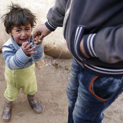 Syyrialaislapsi itkee pakolaisleirillä.