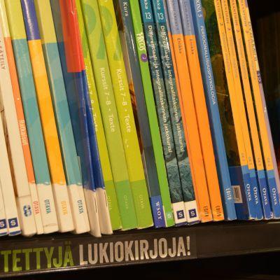 Käytettyjä lukiokirjoja kirjakaupan hyllyssä.