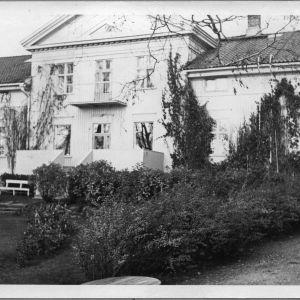 vanha kartano, jonka edustalla puutarha, mustavalkoinen kuva