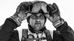 Herman Fogelberg lyfter på slalomglasögonenen med handskar på händerna.