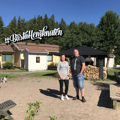 En kvinna och en man står på en innergård i solen.