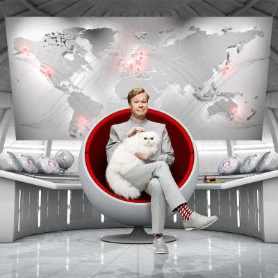 Johan Glans sitter i en rund fotölj likt en skurk från en james bond film. han har en vit angorakatt i famnen.