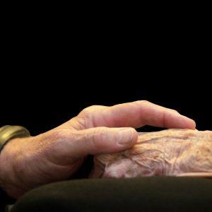 En mans hand håller i en åldrings hand