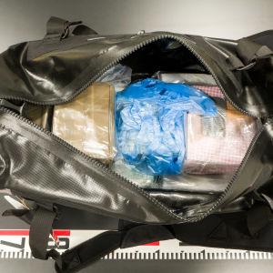 En väska innehållande flera kilo kokain och hasch. Polisen beslagtog väskan i ett grådshus i en hyresstuga i april 2019.