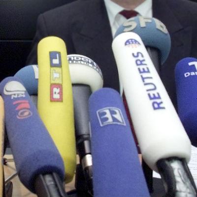 Eri mediatalojen mikrofoneja kohti haastateltavaa.