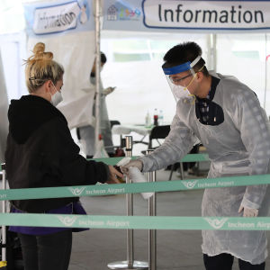 Suojavarusteisiin pukeutunut virkailija suihkuttaa käsidesiä eurooppalaisen matkailijan käsille lentokentällä Etelä-Koreassa
