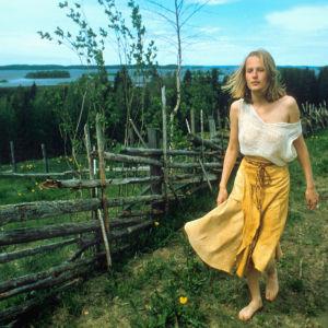 Näyttelijä Sara Paavolainen kävelee aidanviertä Ainon roolissa. Kuva tv-sarjasta Rauta-aika