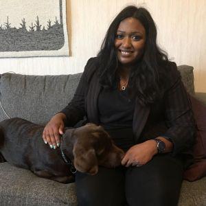 Mörkhyad kvinna i 25-års åldern sitter i soffa med en hund i famnen och ler mot kameran.