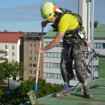 Antti Tervo står på ett sjuvåningshus i Vasa och målar taket.