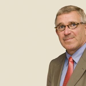 leende man med glasögon beige kavaj blå skjorta röd slips kommunikationsdirektör