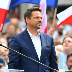 Trzaskowski kannattajiensa keskellä. Taustalla Puolan ja EU:n liput.