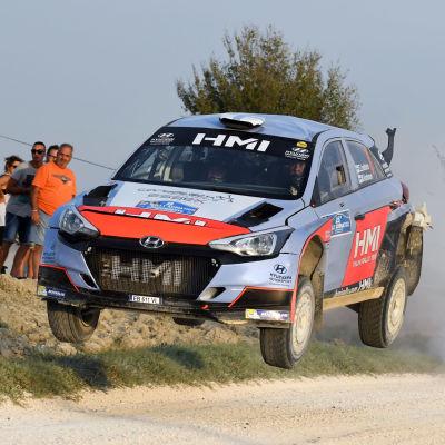 En rallybil kommer i full fart på en grusväg.
