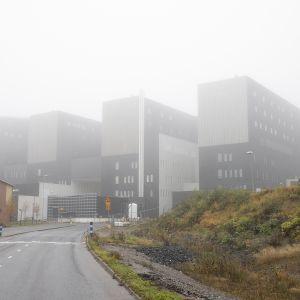 Keski-Suomen keskussairaalan uusi, tummanpuhuva rakennus verhoutuneena usvaan.