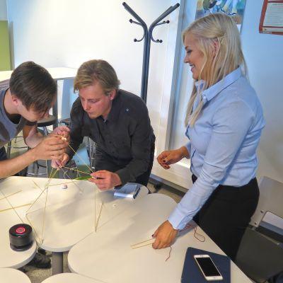 Veli-Matti Järn (keskellä) ryhmänsä kanssa tekemässä spagetti-vaahtokarkki-rakennelmaa.