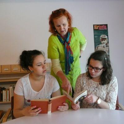 Kaksi lukiolaistyttöä ja opettaja lukevat kirjoja