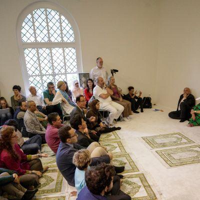 Kuvassa  moskeijan perustaja Seyran Ates ja joukko rukoilijoita, niin miehiä kuin naisiakin, vaaleassa, kauniissa rukoushuoneessa.