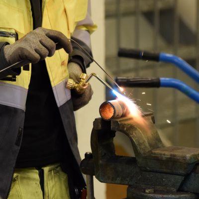 Miehen kädet tekevät hitsaajan töitä