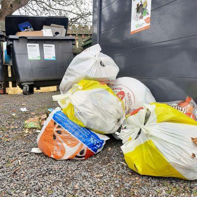 Täysiä roskapusseja maassa roskalaatikon edustalla.