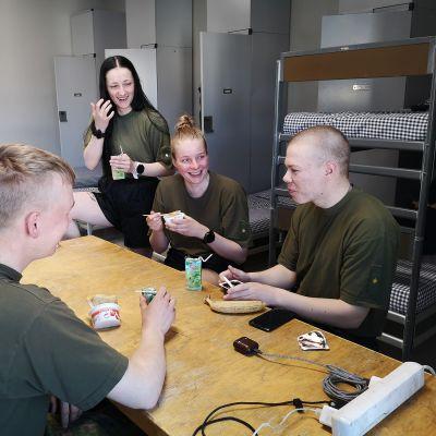 Kuvassa sotilaat syövät eväitä pöydän ääressä.