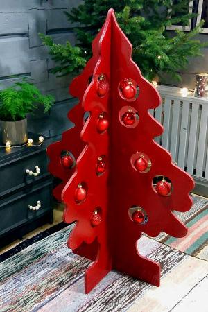 En röd julgran av trä som är monterad av två skivor utformade som en gransiluett. I bakgrunden en liten julgran. Julgranarna är fotograferade i ett vardagsrum med en svart byrå i bakgrunden och trasmattor på golvet. den röda julgranen är dekorerad med röd