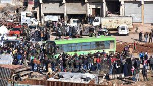 människor köar till en buss för att bli evakuerade i östra aleppo