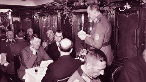 Marsalkka Mannerheim pitää puhetta syntymäpäivävastaanotollaan, istumassa mm. Adolf Hitler ja Risto Ryti (1942).