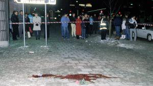 En stor blodfläck, en röd ros och en ensam polis spärrar av platsen där Olof Palme mördades.
