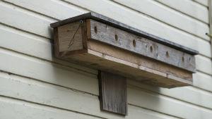 Rivitalomallinen linnunpönttö talon seinässä