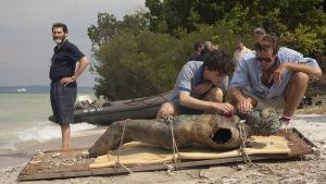Elio (Timothée Chalamet) och Oliver (Armie Hammer) undersöker en staty som de dragit upp ur en sjö. Vid sidan ser man Elios far (Michael Stuhlbarg).