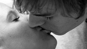 En man kysser en kvinna, svartvit