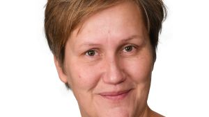 Studioportätt av en kvinna med kort, rödbrunt hår. hon ler lite.
