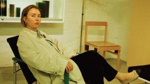 På bilden sitter modeskaparen Carolina Forss i en fåtölj iklädd svarta byxor och en ljus kappa.