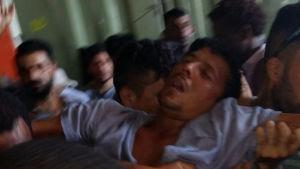 En asylsökande svimmar i tumultet som bryter ut då polisen går in i det stängda flyktinglägret på ön Manus.