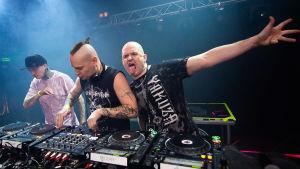 Kolme miestä DJ-pöydän takana, vasemmalla olevalla on musta lippis, violetti t-paita ja tatuointeja, keskimmäisellä, nappuloita vääntävällä pieni ponnarille vedetty irokeesi ja hihaton musta paita, kolmannen, kaljun miehen käsi on levitettynä ilmaan,