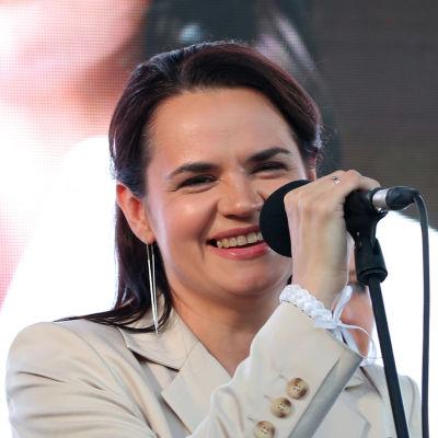 Oppositionsledaren Svetlana Tichanovskaja ler medan hon talar i en mikrofon. En stor bild på hennes ansikte hänger i bakgrunden.