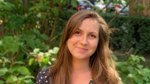 En ung kvinna med brunt hår och pricklig klänning ler mot kameran.