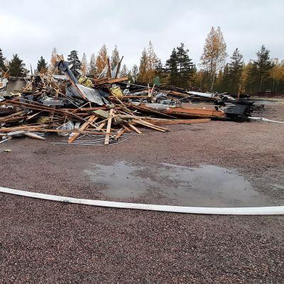 Teollisuushallin tulipalon jäljiltä jäänyttä romua. Etualalla valkoinen pitkä letku ja vesilätäköitä.