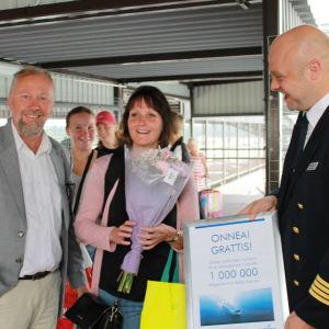 Wasalines miljonte passagerare Johanna Jakobsson står med blommor i handen. Till vänster vd Peter Ståhlberg, till höger kapten Johannes Sjöholm.