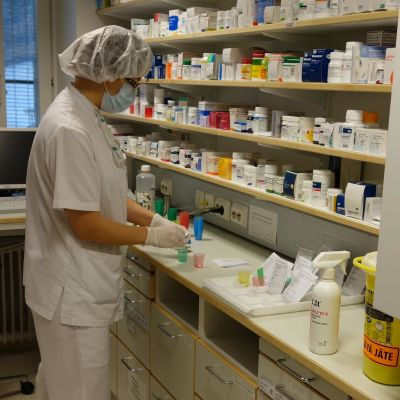 Sairaanhoitaja jakaa lääkkeitä kippoihin
