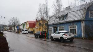Stora Byvägen i Nickby. En gata kantas av höghus på vänstra sidan och trähus i blått, gult och vitt på högra sidan.