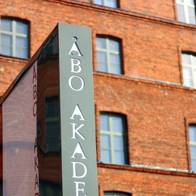 i förgrunden en skylt med texten Åbo Akademi. I Bakgrunden en röd tegelbyggnad.