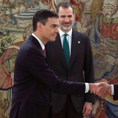 Spaniens nya premiärminister Pedro  Sánchez (till vänster) skakar hand med avgående premiärminister Mariano Rajoy.   Spaniens kung Felipe VI i bakgrunden.